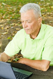 Old man using laptop. On the park bench Royalty Free Stock Photos