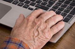 Old man using laptop. Close up of old man hand on keyboard of laptop Stock Photo