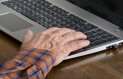 Old man using laptop. Close up of old man hand on keyboard of laptop Stock Photography