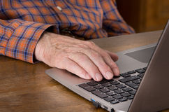 Old man using laptop. Close up of old man hand on keyboard of laptop Royalty Free Stock Photos