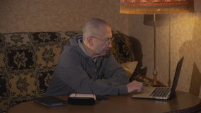 Old man using laptop computer at home. Grandpa sitting at a desk and working at a laptop. Is typing stock footage