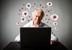 Old man using a laptop. Valentine day and romantic love messages. Old man in white is using a laptop to browse the net. Valentine day and romantic love messages Stock Image