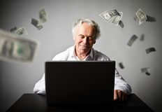Old man using a laptop. Old man in white earns dollars on the in. Old man is using a laptop to browse the net. Old man in white earns money on the internet Stock Image