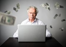 Old man using a laptop. Old man in white earns dollars on the in. Old man is using a laptop to browse the net. Old man in white earns money on the internet Royalty Free Stock Images