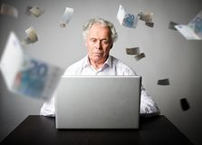 Old man using a laptop. Old man in white earns Euro on the inter. Old man is using a laptop to browse the net. Old man in white earns Euro on the internet Royalty Free Stock Photo