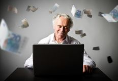Old man using a laptop. Old man in white earns money on the inte. Old man is using a laptop to browse the net. Old man in white earns Euro on the internet Stock Photo