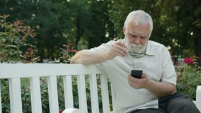 Old Man Using a Phone Outdoors Stock Photography