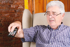 Old man using remote control. Portrait of an old man using remote control and watching tv. Indoors stock photos