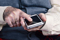 Old man using a smartphone Royalty Free Stock Photography