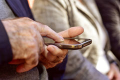 Old man using a smartphone Stock Image