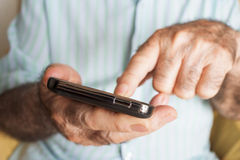 Old man using a smartphone Stock Photography