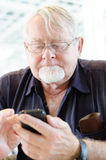 Old man using smartphone Royalty Free Stock Photography