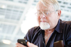 Old man using smartphone Stock Photography