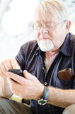 Old man using smartphone Stock Photos