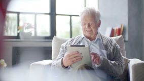 Old man is using tablet computer at home stock footage