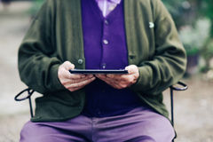 Old man using a tablet computer outdoors. Closeup of an old caucasian man using a tablet computer outdoors stock photography