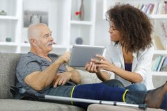 Old man using tablet with help assitant Royalty Free Stock Photo