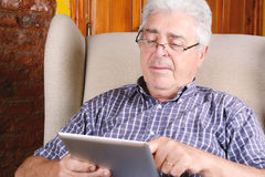 Old man using tablet. Royalty Free Stock Photo