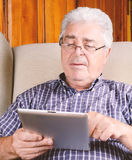 Old man using tablet. Royalty Free Stock Photography