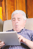 Old man using tablet. Stock Images