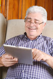 Old man using tablet. Royalty Free Stock Images
