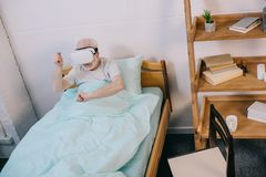 Old man using virtual reality headset. In clinical bed Stock Photo