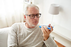 Old man using voice command recorder on smartphone. Technology, people, lifestyle and communication concept - close up of senior man using voice command recorder Royalty Free Stock Photos