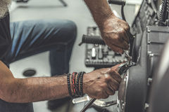 Old man using wrench for repair. Mature biker is squatting near motorcycle and renovating it. Close up of male hands holding tools. Top view Royalty Free Stock Images