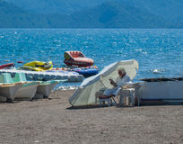 Old man on vacation in Marmaris. MARMARIS, TURKEY - MAY 2017 - old white-bearded man dressed white reading a newspaper under the white umbrella with sea and royalty free stock image