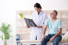 The old man visiting young male doctor. Old men visiting young male doctor stock images