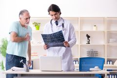 Old man visiting young male doctor. The old men visiting young male doctor royalty free stock images