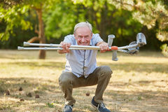 Old man with vitality and crutches. In rehab having fun Stock Photo