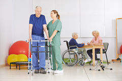 Old man with walker during pyhsiotherapy Stock Photos