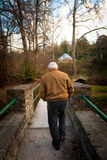 Old Man Walking Across a Bridge Outside Royalty Free Stock Photo