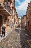 Old man walking by alley in the city center of Ferrara. Stock Image