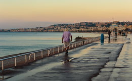 Old man walking along the Promenade des Anglais in Nice morning Royalty Free Stock Image
