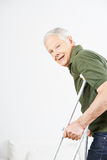 Old man walking with crutches Stock Image