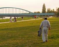 Old Man Walking Down The Promenade. Grandpa walking down the river bank promenade, Zagreb, Croatia royalty free stock photos