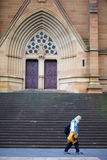 Old man walking in front of church Stock Image