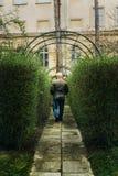 Old man walking in green valley in botanical garden in spring ti. Me Royalty Free Stock Photo