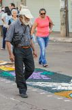 Old man walking and looking at the sawdust art on the street. Campo Grande, Brazil - May 31, 2018: Holiday event of Corpus Christi at the 14 de Julho street Stock Image