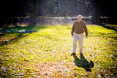 Old Man Walking Outside in the Fall Stock Photography