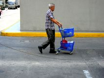 An old man walking and pushing a grocery cart Royalty Free Stock Photography