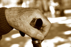 Old man with a walking stick, in sepia toning. Closeup of the hand of an old caucasian man with a walking stick, in sepia toning stock photos
