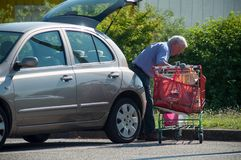 Old man walking with trolley on supermarket parking storing his packages in his car. Mulhouse - France - 21 June 2018 - old man walking with trolley on Stock Photography