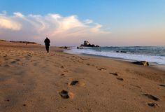 Old Man Walks Along the Shoreline. An old man walks along the shoreline towards a chapel in the background at the beach Stock Photography