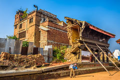 Old man walks around a building destroyd by earthquake in Nepal Stock Images