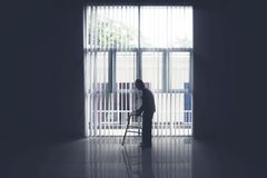 Old man walks near the window with a walker. Silhouette of lonely old man walking near the window with a walker Royalty Free Stock Photography