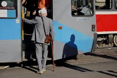 Old man with a wand is trying to climb in tram royalty free stock photography