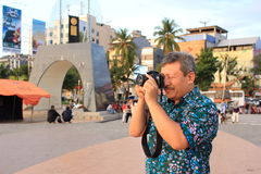 Old man was taking pictures. An old man is practicing his hobby of taking pictures using a camera from his son. The man was on the beach in the city of Makassar royalty free stock images